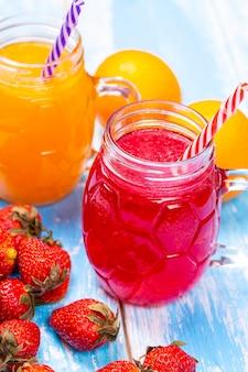 青い木製のテーブルの上のオレンジとイチゴのジュース