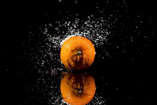오렌지는 검은 배경에 서있다.