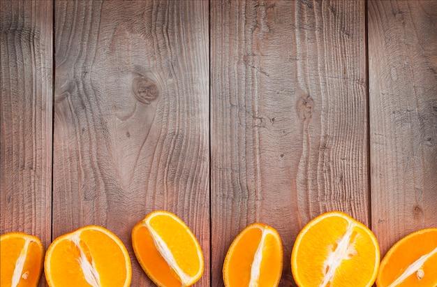 유기농 오렌지 과일. 나무 배경에 조각입니다.