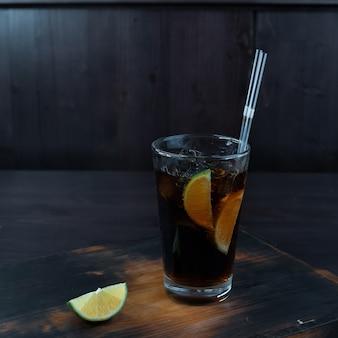 Оригинальный вкусный коктейль с добавлением льда, виски и кока-колы, дольки лайма стоит на деревянном столе в ресторане. оригинальная подача алкогольных напитков в баре.