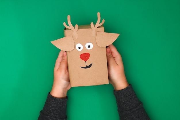Оригинальный дизайн рождественского подарка из крафт-бумаги в виде оленя на зеленом фоне