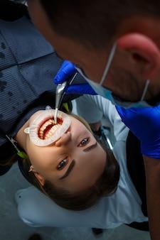 歯科矯正医は患者の歯に金属製のブレースを付けます。歯科矯正歯科治療。高品質の写真