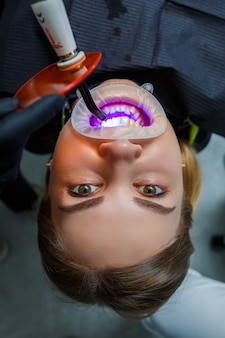 Ортодонт ставит на зубы пациента металлические брекеты. ортодонтическое лечение зубов. фото высокого качества