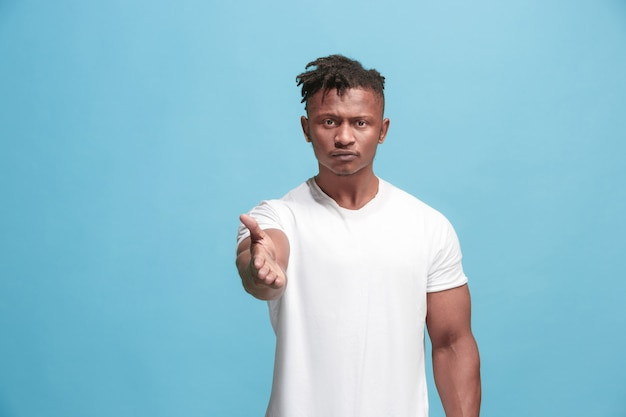 圧倒的なアフリカ系アメリカ人のビジネスマンがあなたを指してあなたを望んでいる、青い壁に半分の長さのクローズアップの肖像画