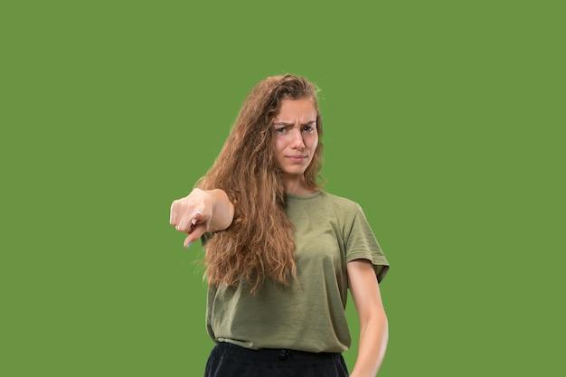 Властная бизнес-леди указывает на вас и хочет вас, портрет крупным планом половинной длины на зеленом фоне.