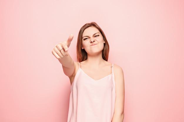 屈辱的な女性があなたを指してあなたを望んでいる、ピンクの壁に半分の長さのクローズアップの肖像画