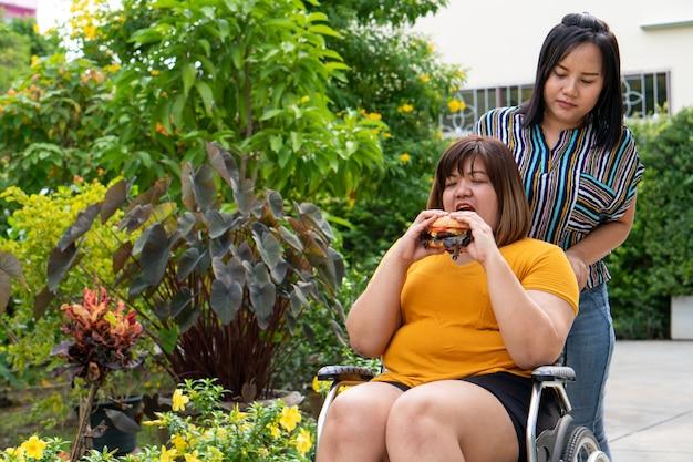 과체중 여성은 휠체어를 타고 햄버거를 먹습니다.
