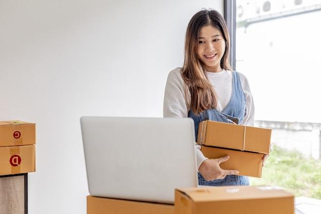 オンラインストアの所有者は、2つの小包ボックスを持っており、注文残高を確認して、商品を梱包するための小包である配達の準備をしています。オンライン販売とオンラインショッピングの概念。
