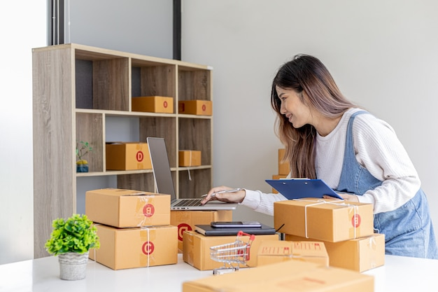 オンラインストアの所有者は、ラップトップから購入金額を確認し、商品を梱包するための配達、小包を準備しています。オンライン販売とオンラインショッピングの概念。