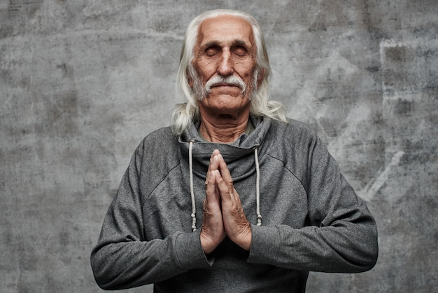 Умиротворенный седовласый дедушка сложил ладони в молитвенном положении, медитации, расслаблении, прощении, сохранении спокойствия. серый фон студии