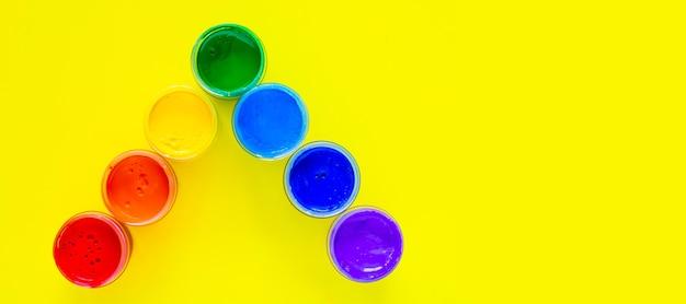 Банки с краской стоят под углом, цвета отображаются в порядке радуги на желтом ба ...