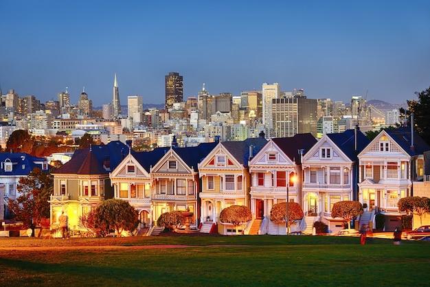カリフォルニア州サンフランシスコのペインテッド・レディは、夕日と高層ビルを背景に輝いています。 Premium写真