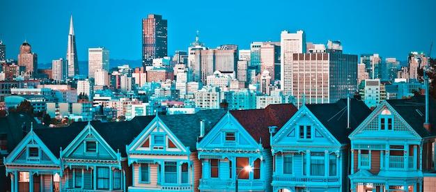 カリフォルニア州サンフランシスコのペインテッド・レディは、夕日と高層ビルを背景に輝いています。