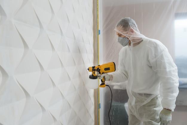 画家はスプレーガンで3d壁をペイントしています。