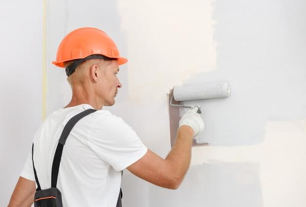 화가는 롤러로 방에 벽을 그리고 있습니다.