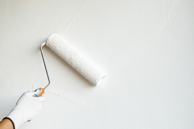 Художник красит стены в белый цвет и украшает интерьер домашней гостиной.