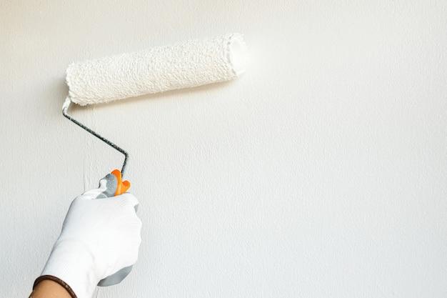 화가는 벽을 흰색으로 칠하고 집 거실의 내부를 장식하고 있습니다.