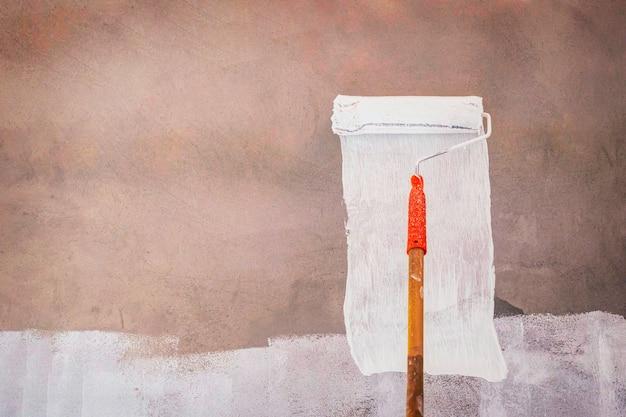画家は毛皮のローラー、背景、背景で壁をペイントします