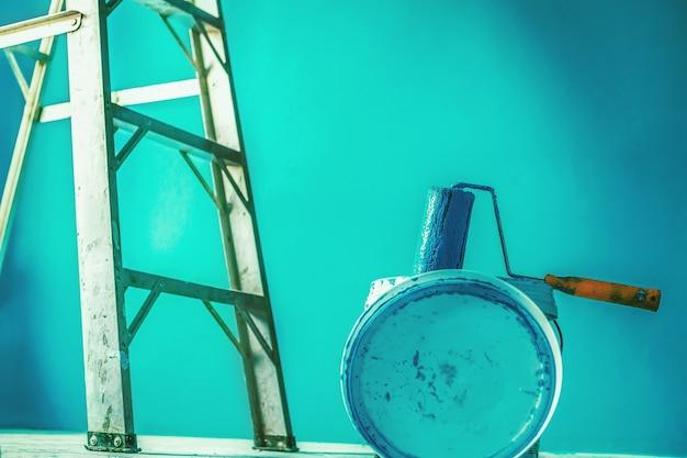 Художник расписывает стену меховым валиком, задник, фон.