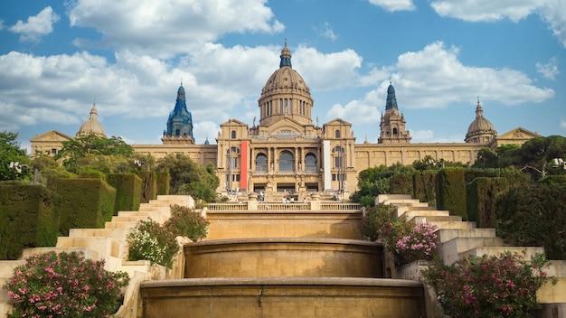 Национальный дворец в барселоне, сады испании и люди перед ним. облачное небо