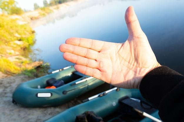 川の土手に駐車した、早朝に釣り道具を持った2隻のゴム製インフレータブルボートを背景に、オールからのマゾールを持った男の手のひら。