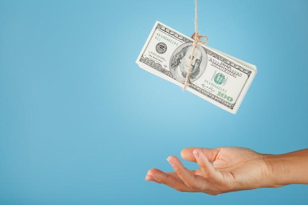 손바닥은 파란색 배경에 밧줄에 매달린 돈에 닿습니다.