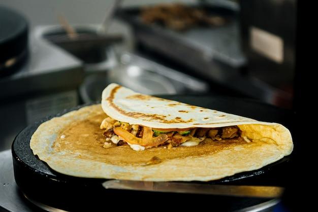 Блин обжаривается и готовится на большой сковороде для приготовления чугунных роти. индийская традиционная уличная еда. тайский блинчик с бананом, ветчиной и сыром.
