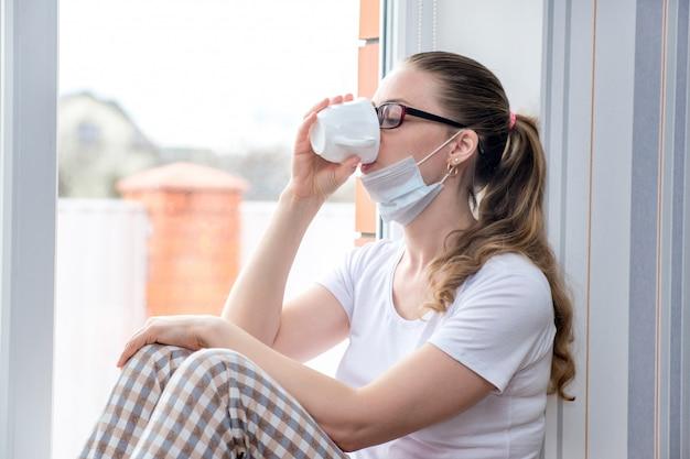 コロナウイルスの流行。自宅検疫。病気休暇の白人女性は薬用お茶を飲んで、医療用防護マスクの窓に座っています。