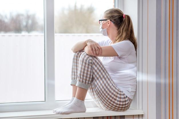 Пандемия коронавируса. домашний карантин. кавказская женщина на больничном сидит у окна в медицинской защитной маске