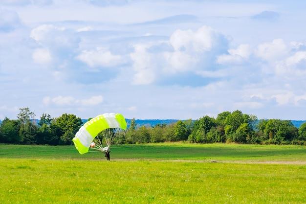 Парашютист приземлился на травянистом поле. прыжки с парашютом. прыжки с парашютом.
