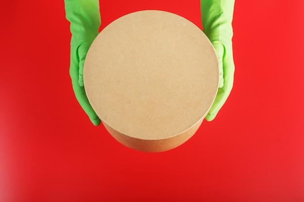 빨간색 배경에 녹색 고무 장갑과 손에 배달 서비스에서 소포.
