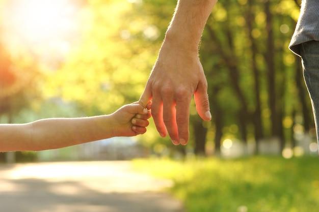 행복한 배경으로 아이의 손을 잡고 부모