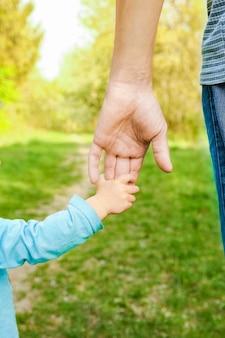 幸せな背景で子供の手を握っている親