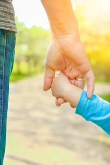 Родитель держит ребенка за руку