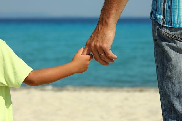 親は夏にビーチで子供の手を握ります