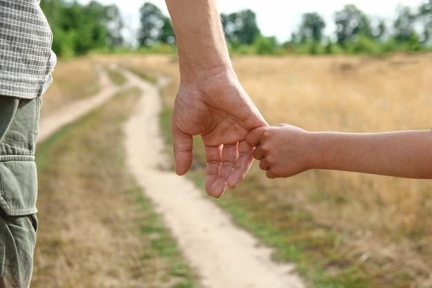 Родитель держит за руку маленького ребенка возле тропы