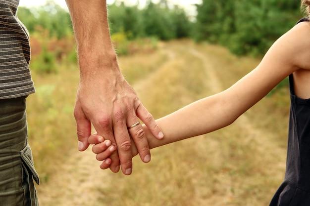 親は自然の中で小さな子供の手を握っています