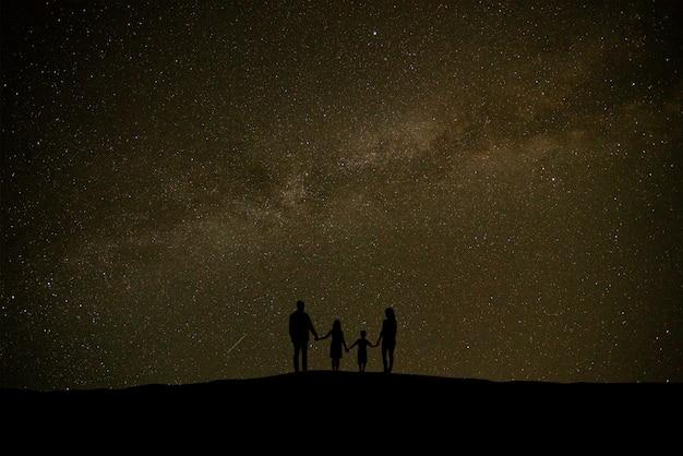 별이 빛나는 하늘을 배경으로 서 있는 부모와 아이들