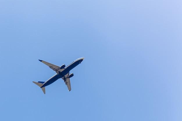 Пассажирский самолет на фоне голубого ясного неба в солнечный день.