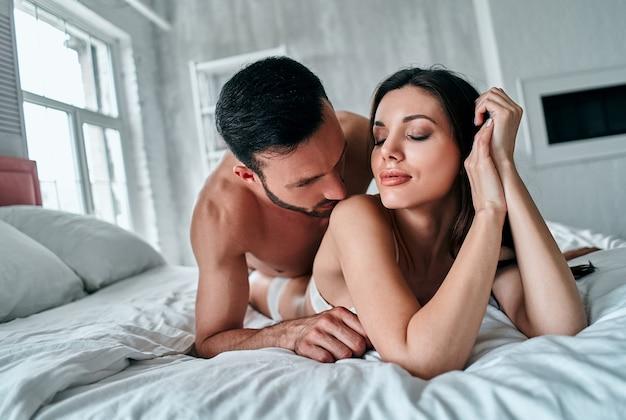 ベッドに横たわっている下着の情熱的なカップル