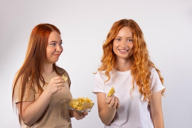 Redhaired 여자 친구 여자의 취미는 흰 벽에 감자 칩을 먹는다