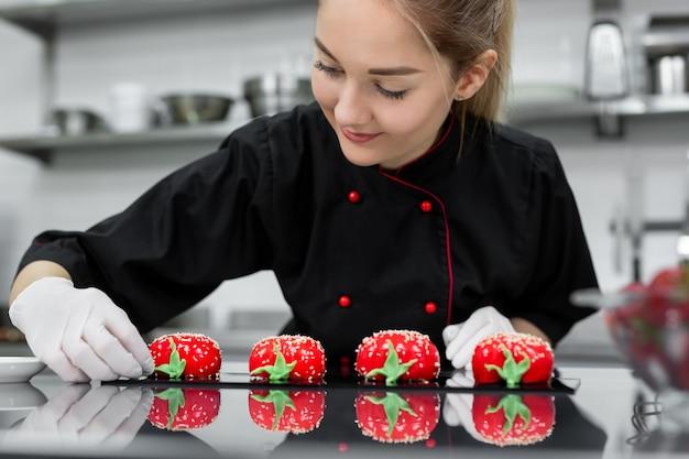 パティシエが赤いムースケーキをイチゴのように飾ります。