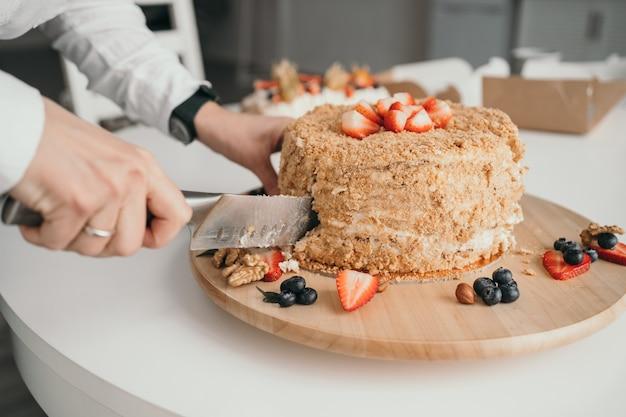 ペストリー シェフがケーキを切っています。おいしいハニー ケーキがナイフでカットされています。ハニー ケーキのクローズ アップ