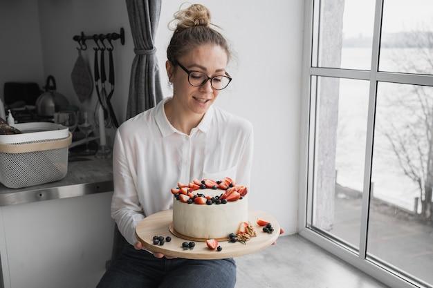생과자 요리사는 딸기와 블루 베리로 장식 된 딸기 아름다운 케이크와 함께 식욕을 돋우는 수제 케이크 생일 케이크를 들고있다