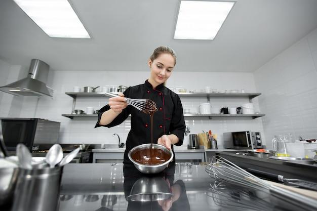パティシエはチョコレートガナッシュと泡立て器を混ぜます。