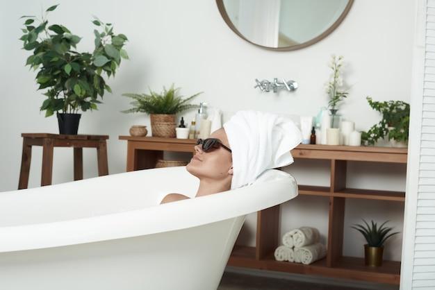 白斑を持った哀愁を帯びた美しい少女は、猫のサングラスと頭にタオルをかけたお風呂に横たわっています。ファッション、スキンケア、スタイルのコンセプト。