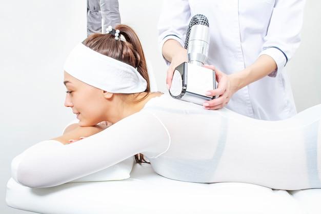Пациент делает процедуру массажа сжиженного нефтяного газа, чтобы отрегулировать вес и фигуру, избавляясь от целлюлита.