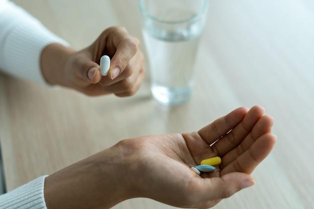 患者は薬を手に持っています。病気を治療したり、人々のためにビタミンサプリメントを摂取したりするための薬は栄養失調です。