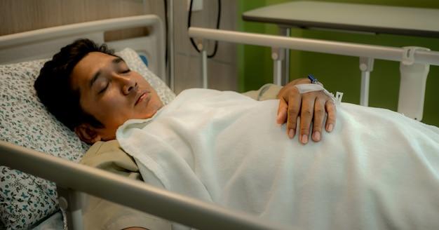 病棟のベッドにカニューレを持った患者の男性の手