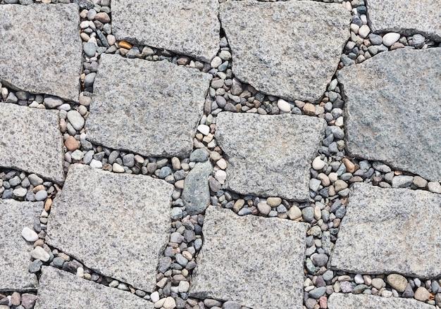 포장 도로는 가장자리가 고르지 않은 슬래브 형태의 돌과 그 사이에 자갈로 만들어져 있습니다. 디자이너를위한 조직 상 추상적 인 배경입니다.
